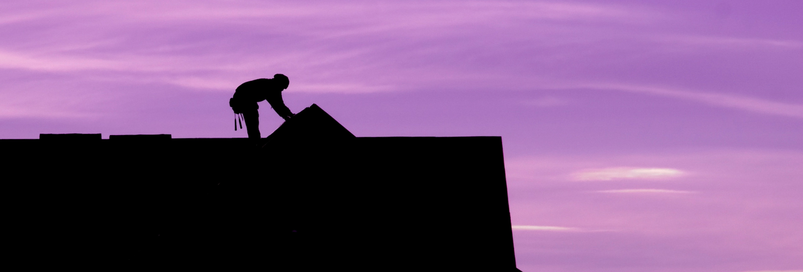 silhouette of worker on roof against a purple sky