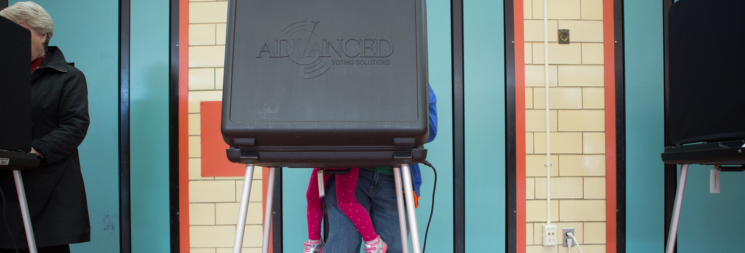 parent and childs legs behind a voting booth