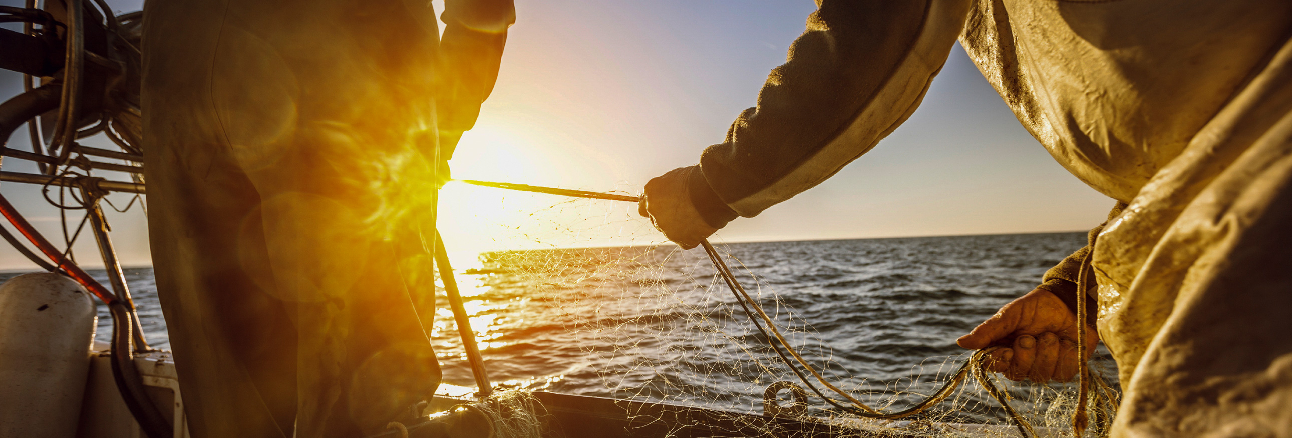 fisherman tying nets on board a boat with sun in background