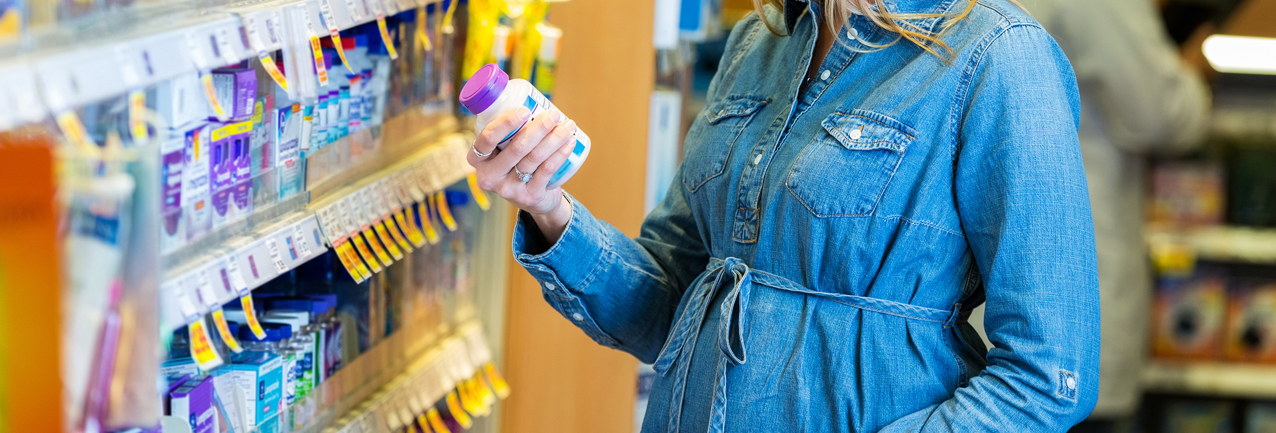 woman browsing vitamin bottles in a store