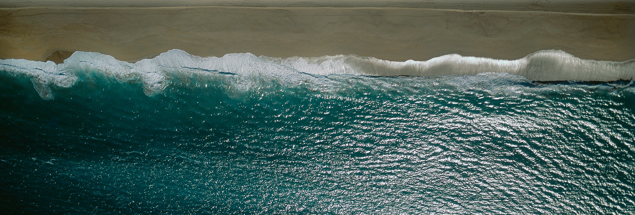 aerial view of a wave crashing on beach