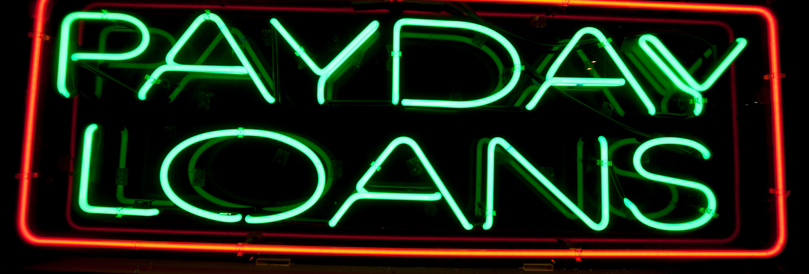 neon sign that reads payday loans
