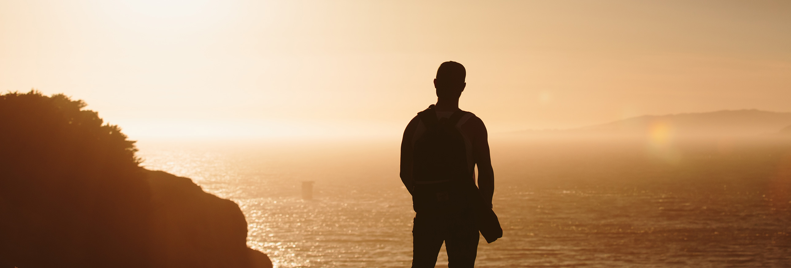 silhouette of a man overlooking water at sunset