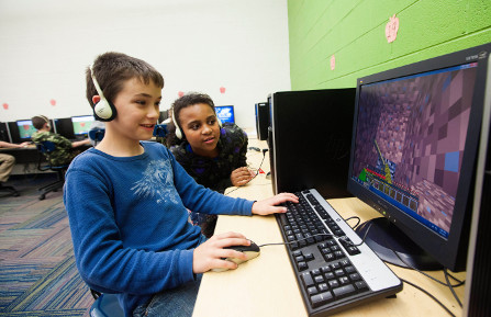 young boy and girl with headphones sit in front of computer