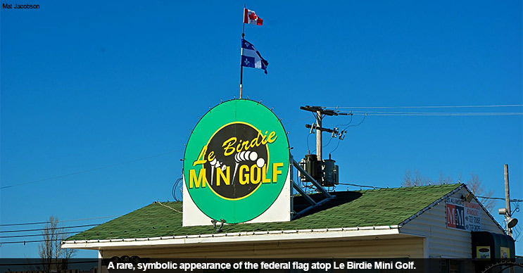 A rare, symbolic appearance of the Canadian flag atop Le Birdie Minigolf.