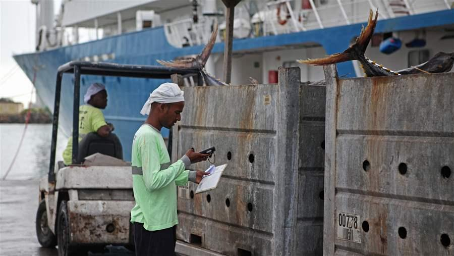 A dock worker in Port Victoria, Seychelles, enters data on recently landed tuna catch.