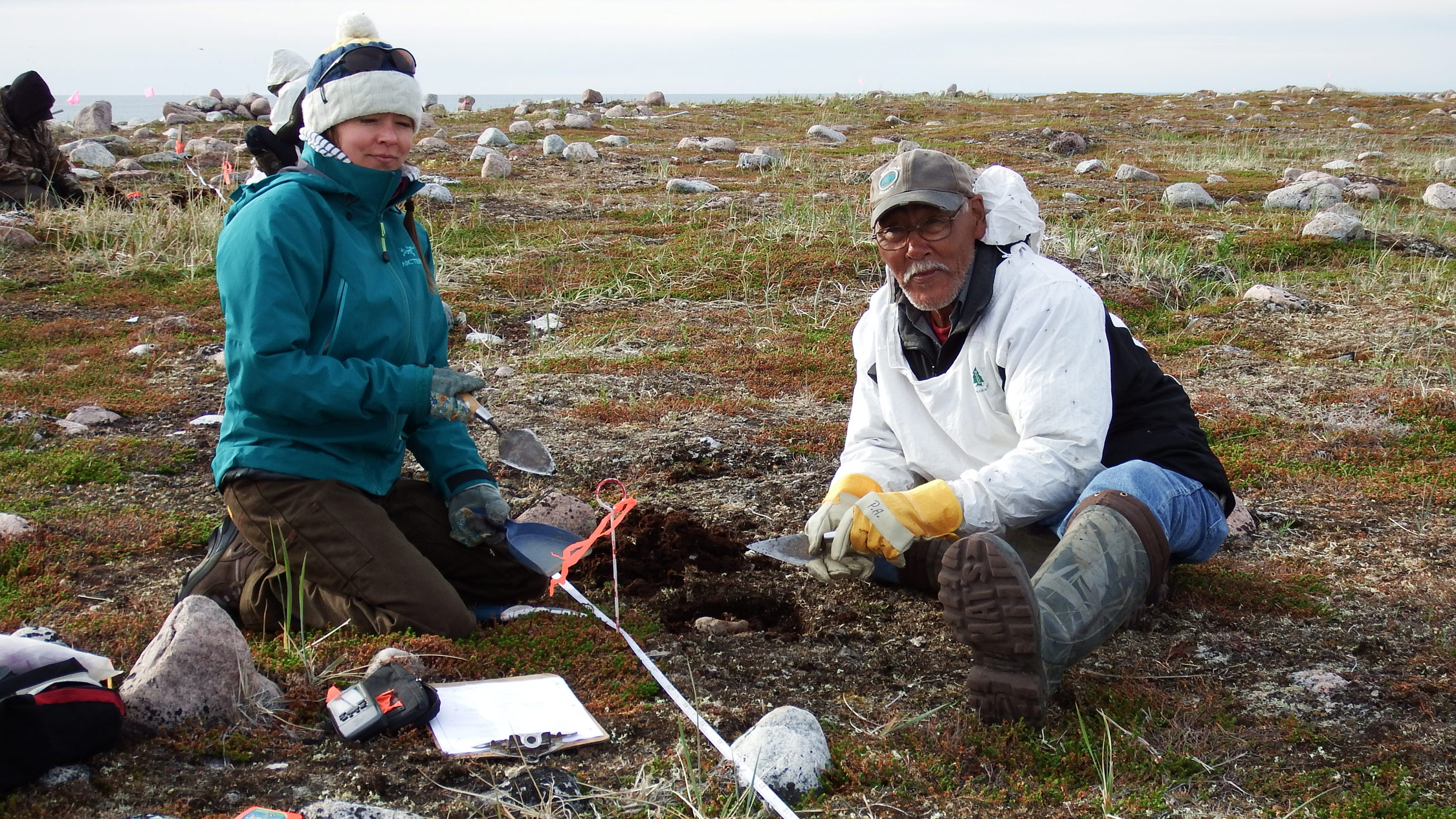 Kristin Westdal, a marine biologist with Oceans North Canada, conducts a shovel test with Peter Alareak of Arviat, Nunavut.