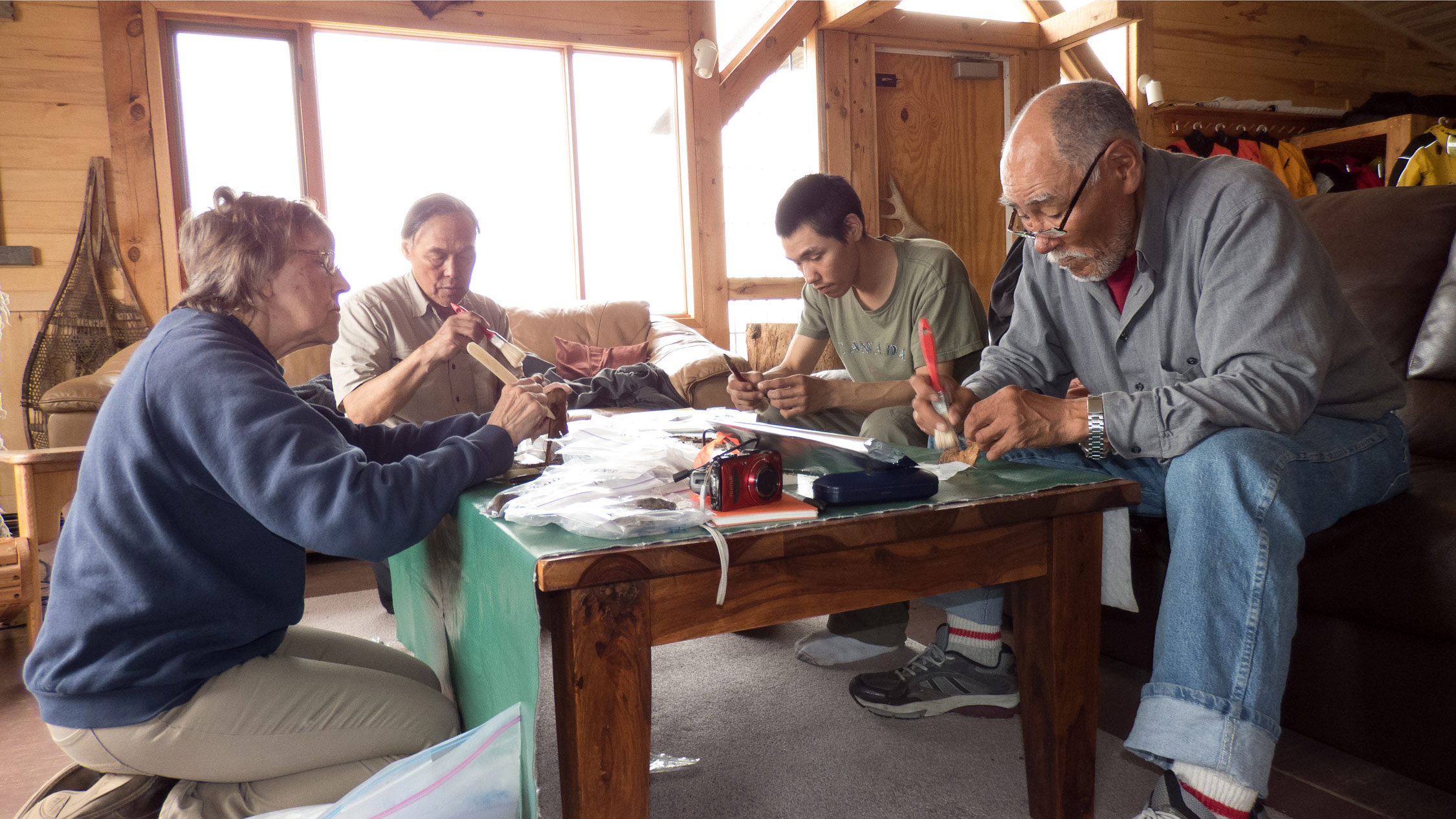 Preparing artifacts for carbon dating and other analyses at the lodge, from left: Virginia Petch, Luke Suluk, David Tassiuk, and Peter Alareak.
