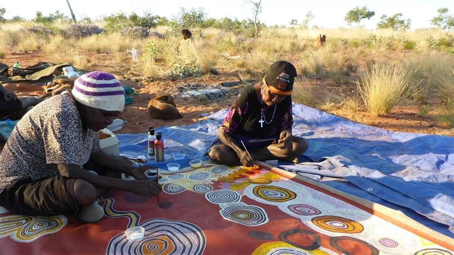 Pintupi Traditional Indigenous Owners painstakingly create a group painting to celebrate the new IPA.