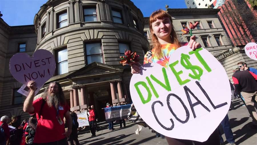 Activists demonstrate outside City Hall in Portland, Oregon, urging the mayor to divest the city's holdings in fossil fuel companies. Several states are considering bills that would have state pension systems divest their coal and oil stocks. (AP)