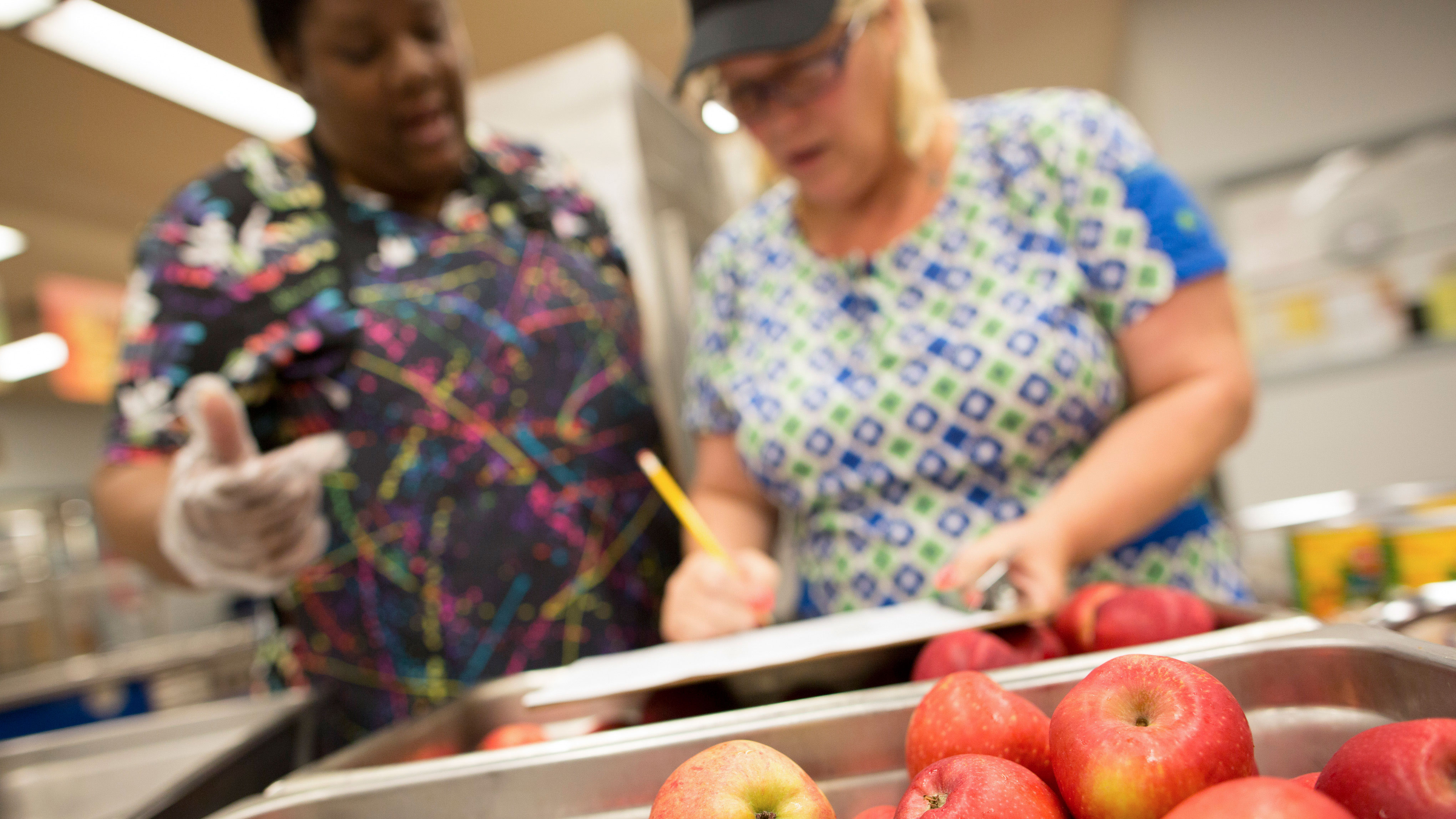 Cafeteria staff prepare school lunches for students.