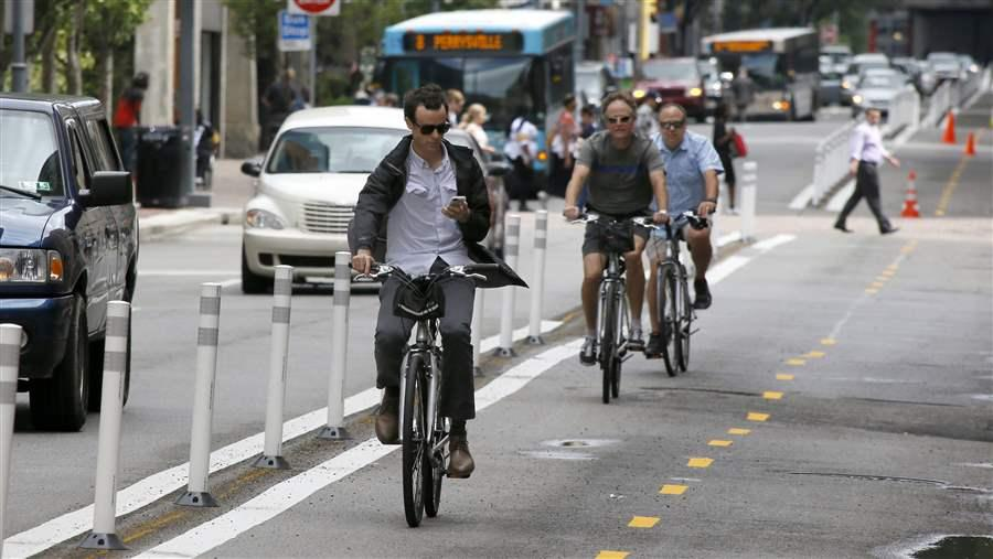 A bicyclist looks at an electronic device