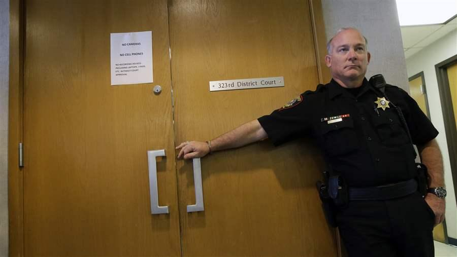 A guard stands outside a juvenile courtroom