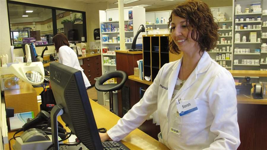 Pharmacist Sarah Burke checks a prescription drug database