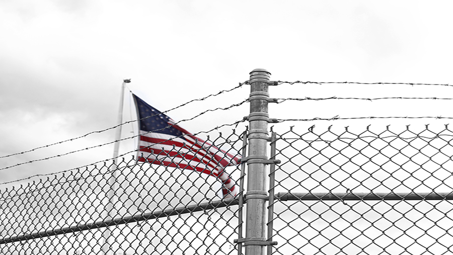 American flag behind barbed wire fence