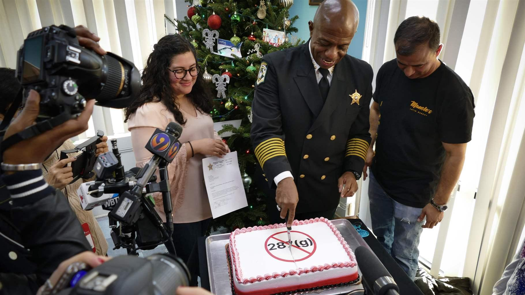 Sheriff Garry McFadden of Mecklenburg County, North Carolina, celebrates his election in November by slicing a cake frosted with a message in protest of 287(g), the federal immigration enforcement and deportation program he pledged to end in the county. An increase in arrests related to the program is losing steam as more big-city sheriffs back out of it, even as more smaller counties in conservative areas join up.
