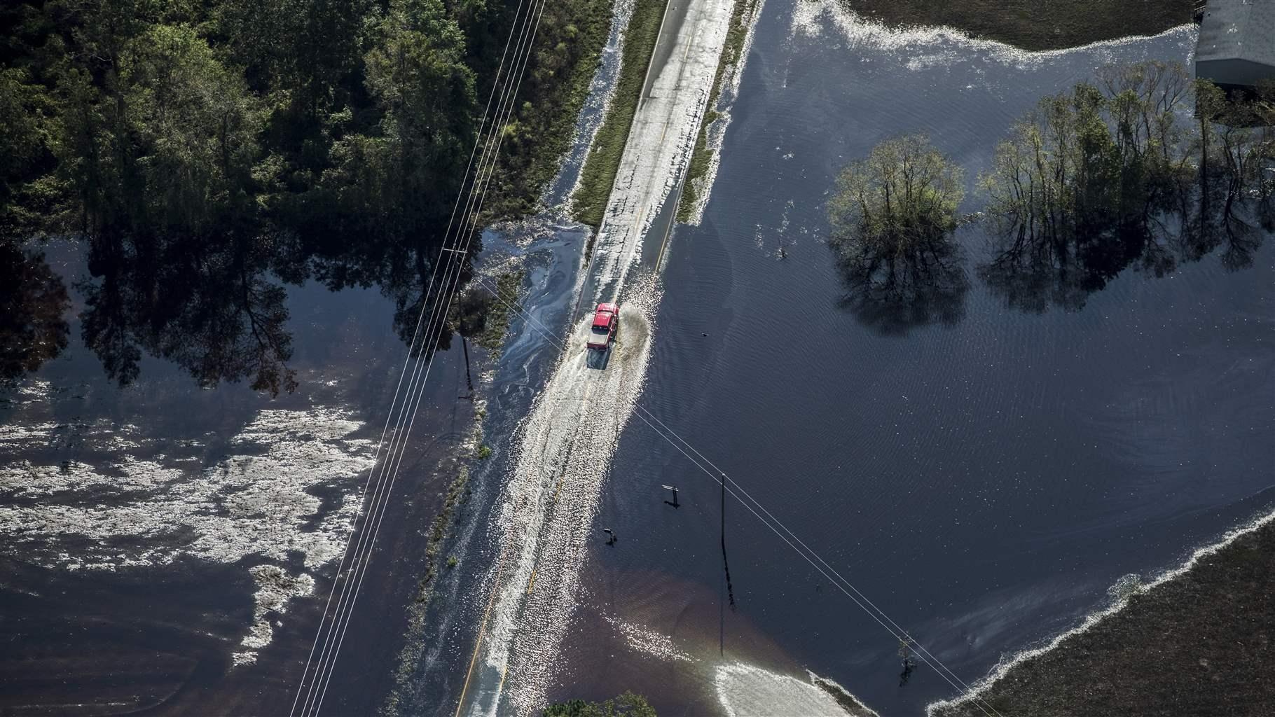 truck drives through floodwater