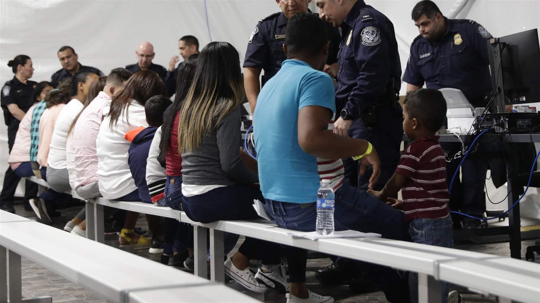 Migrants wait to apply for asylum