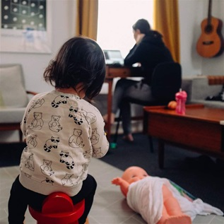 Child with parent working from home