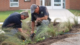Jim Stipe (left), Public Works Director of Swansboro, North Carolina, and a Town of Swansboro employee plant a rain garden at the city's Town Hall.
