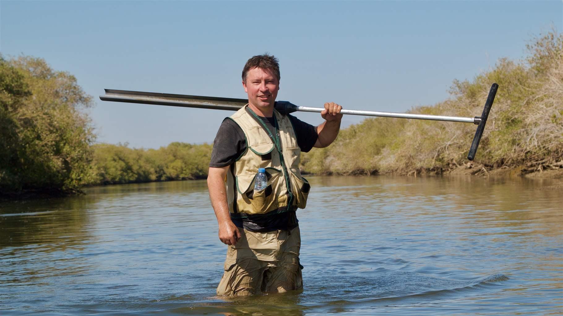 Steve Crooks holding equipment in water in Khor Kalba