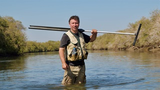 Steve Crooks holding equipment in water in Khor Kalba