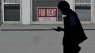 man walks past a For Rent sign