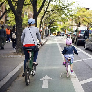 Mother and daughter riding bicycles in city