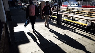 People walk on a business street in San Mateo, California, the United States, Feb. 21, 2021