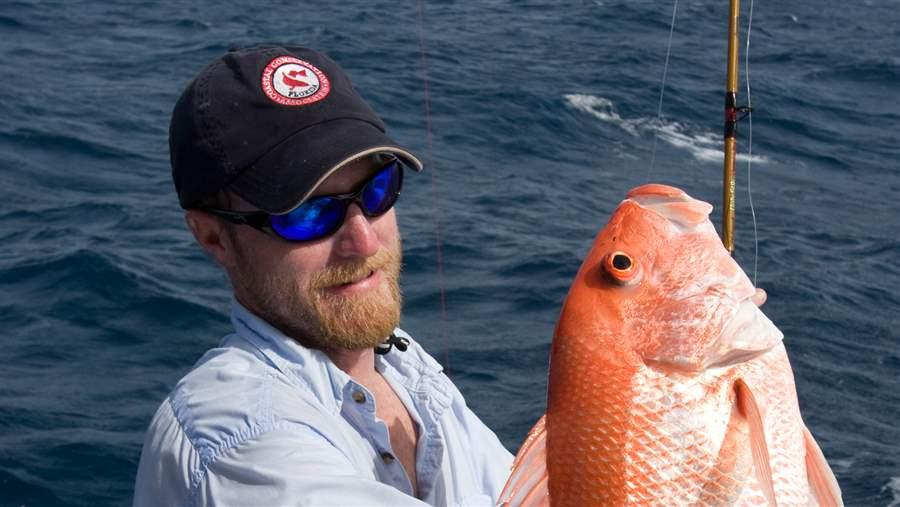 Fisherman holding Adult Red Snapper