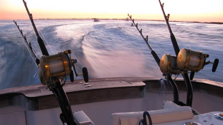 Close up of fishing rods on boat at sunrise Mexico