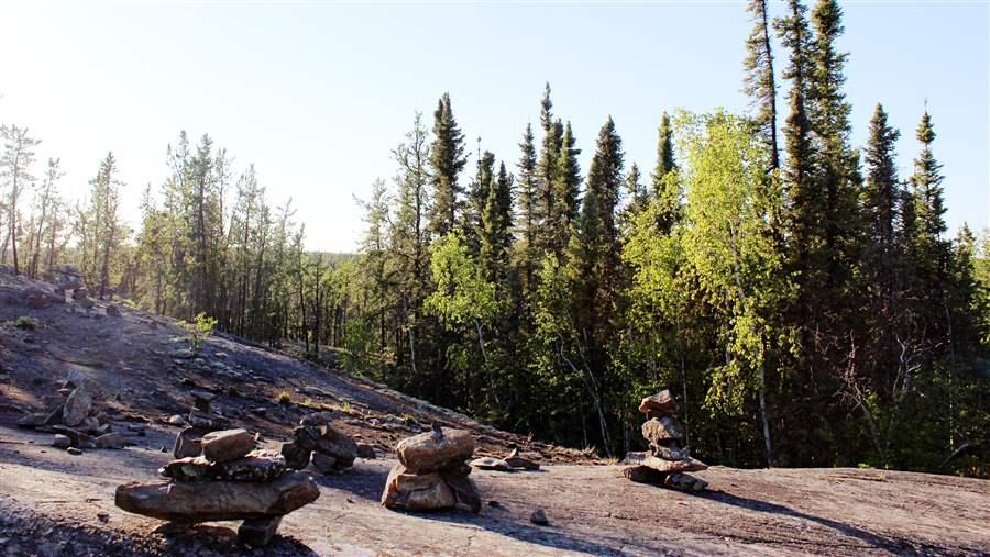Inukshuk, or manmade stone landmarks, line the Cameron Falls Trail in the boreal forest region of Canada's Northwest Territories.