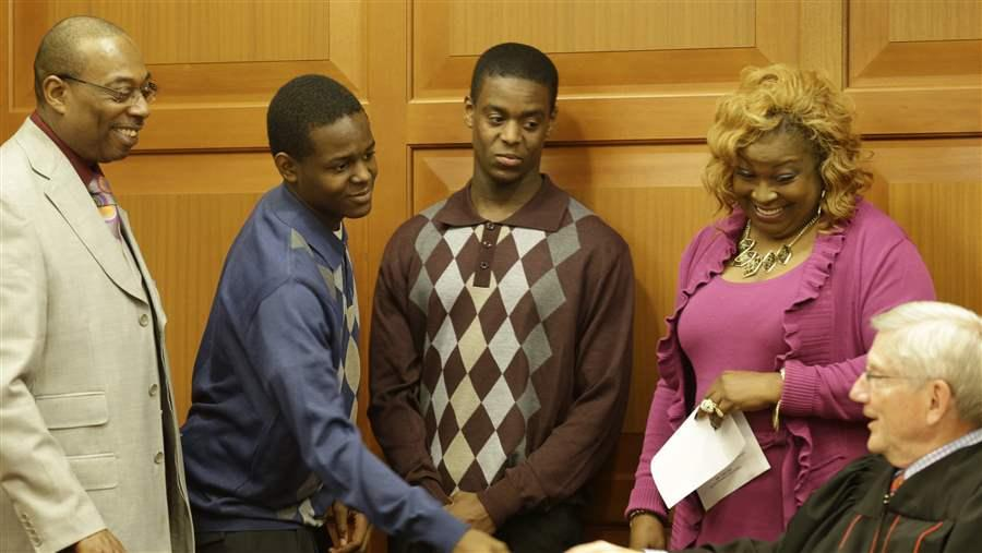 Jamal Byers, left center, shakes hands with Judge James Cissell, right, after Jamal and Tyshawn Byers, right center, were adopted by the Rev. Edward Byers, left, and his wife Darnette Byers, last November in Cincinnati. Adoption is a desired outcome for many neglected or abused children. (AP)