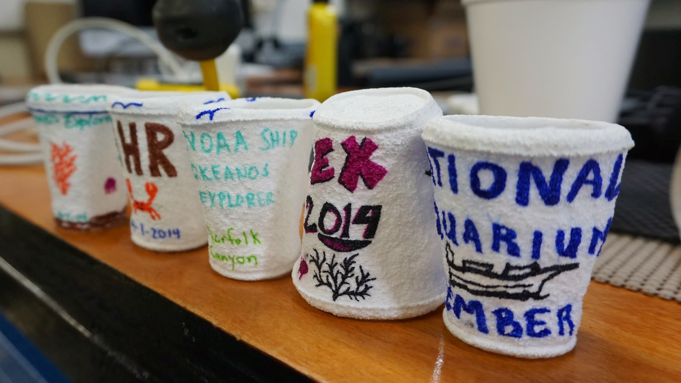 A rite of passage: Each Okeanos guest drew on a plastic foam cup. After the cups were submerged at 2,200 feet, the water pressure shrank them to one-third of their original size.