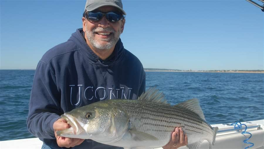 Lee Crockett poses with his catch—a 15-pound striped bass—before releasing it to swim another day.