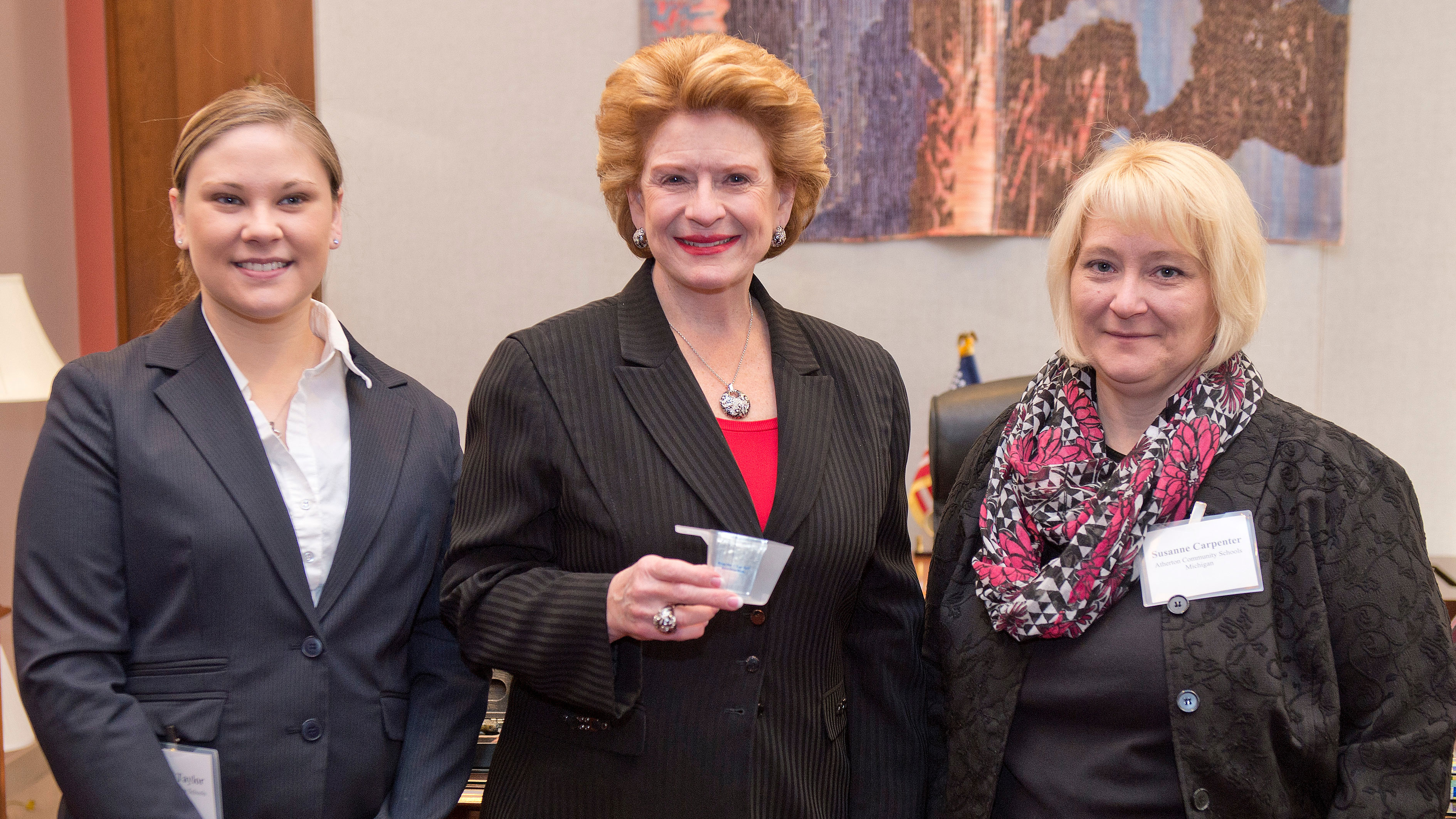 Food service director Bethany Taylor (left) and principal Susanne Carpenter (right), representing Atherton Community Schools in Michigan, show Senator Debbie Stabenow (D-MI) the half-cup portion that students must take of fruits or vegetables with every lunch. A recent survey found that 91 percent of parents nationwide support requiring schools to include a serving of fruits or vegetables with every meal.