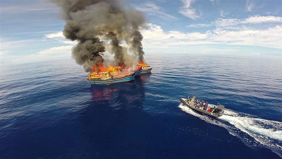 burning illegal fishing vessel and government boat in Palau