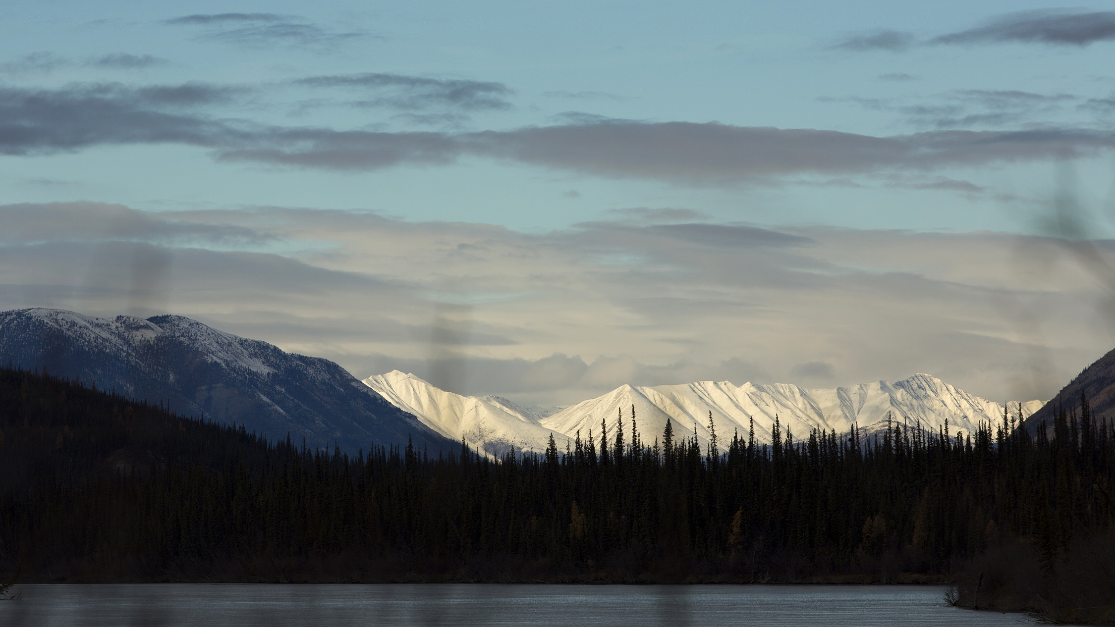 The Mackenzie Mountains loom above trees lining the 335-mile-long South Nahanni River