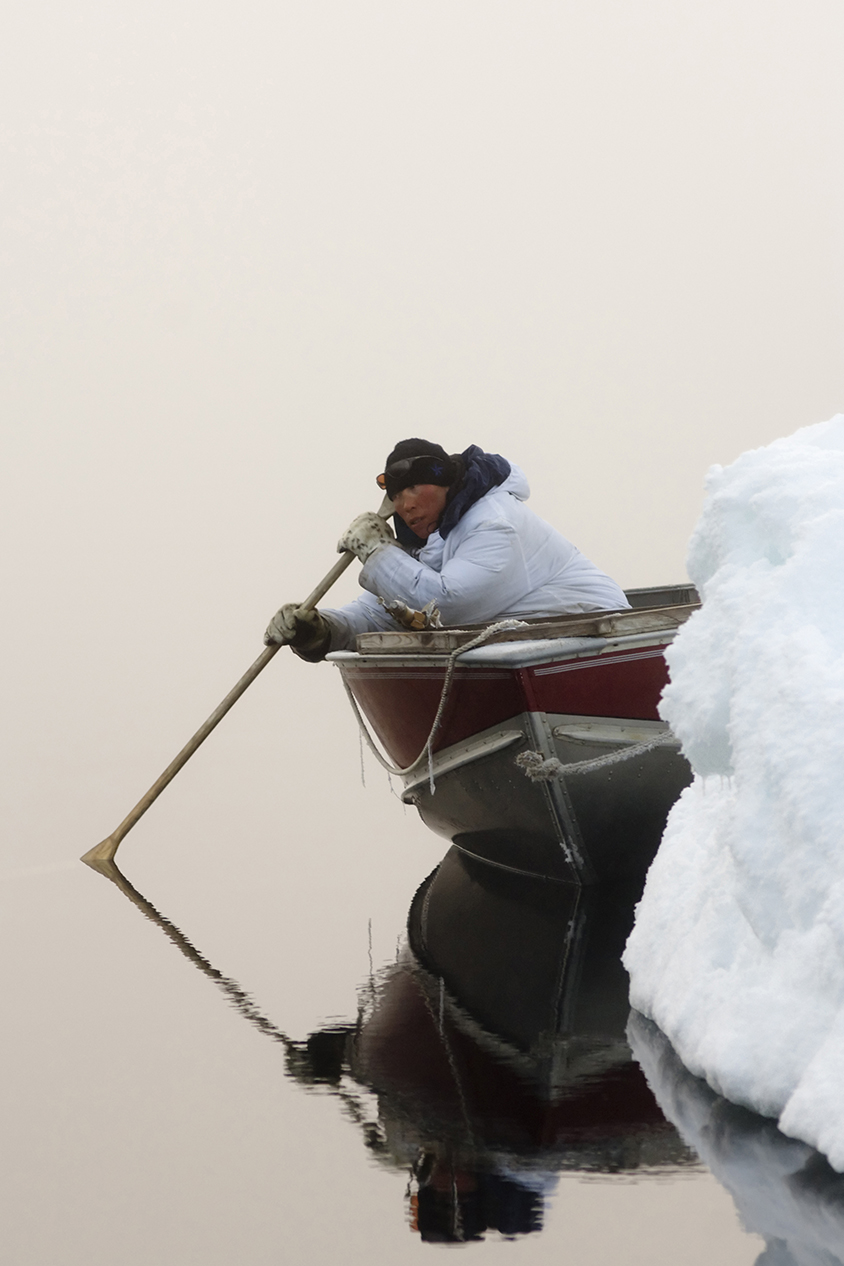 An Inupiat hunter uses a wooden oar to listen for passing bowheads during the spring whaling season in the Chukchi Sea.