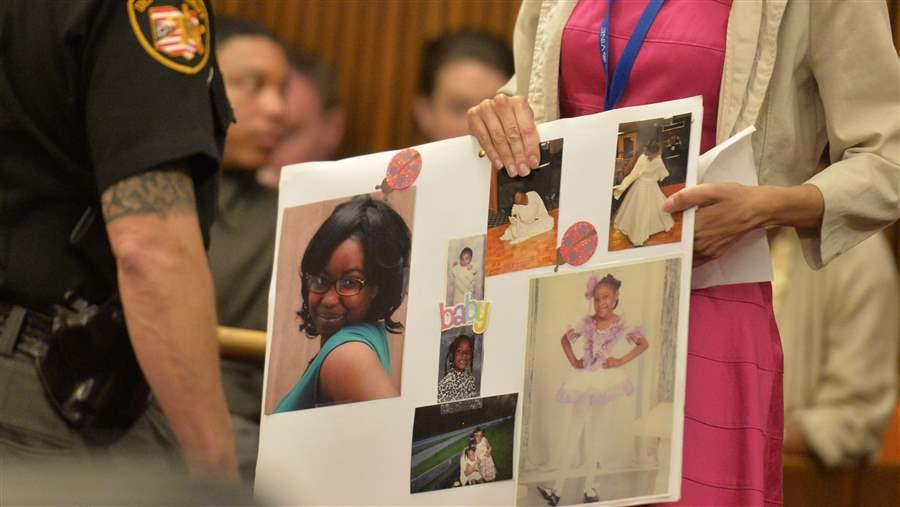 court worker holds a board of photos