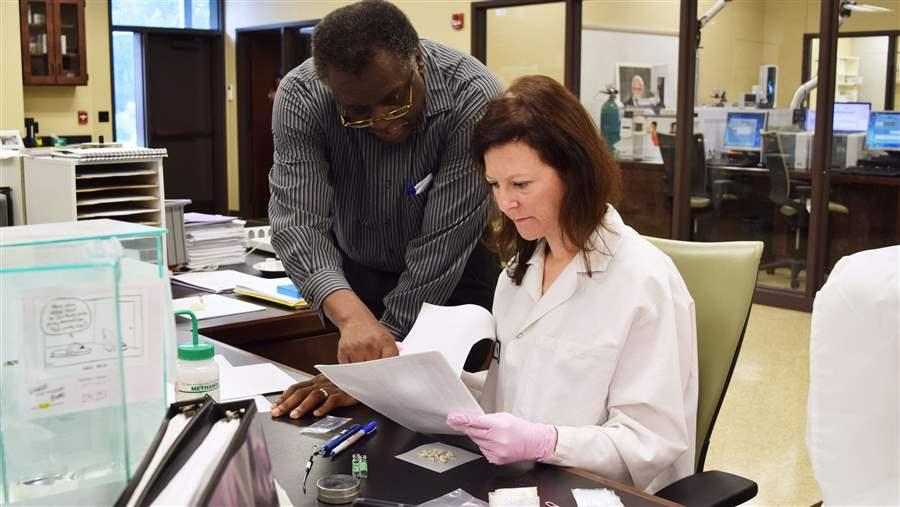 Forensic scientist Pamela Kitchens and lab director Sherwin Boswell examine heroin at a lab