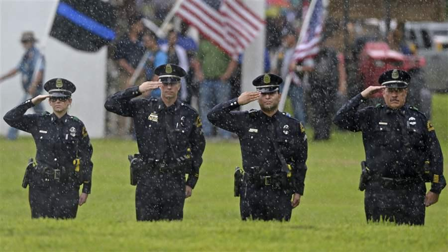 Members of the Dallas Police Department salute the casket carrying Baton Rouge police officer Montrell Jackson