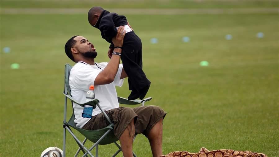 "Joseph Arradondo plays with his son during his daughter's soccer game in Brooklyn Park, Minnesota. Arradondo attended a Minnesota ""co-parent"" court that helps separated couples divvy up parenting responsibilities."