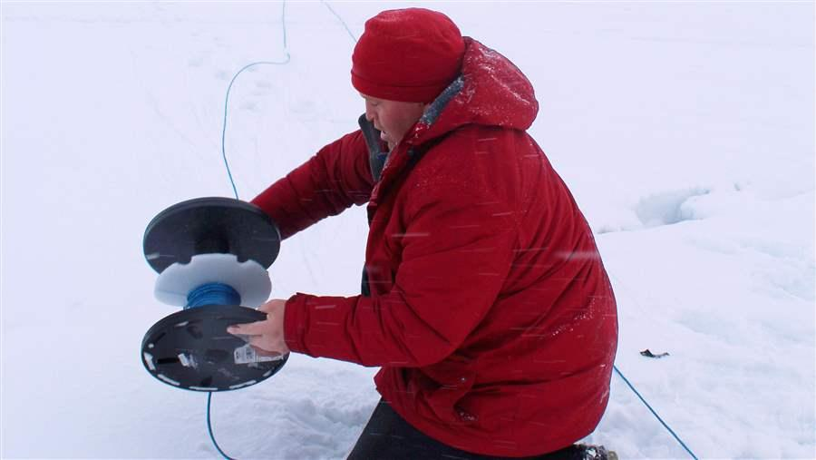 Alex Ootoowak unwinds more than 150 metres of rope before deploying the first hydrophone through the ice in Milne Inlet.
