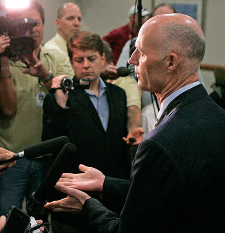 Rick Scott with reporters
