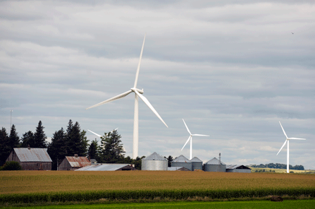 Iowa Wind Farms Wind Turbines Spin Over a Farm