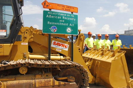Constructions equipment with wokers and a sign for the American Recovery and Reinvestment Act