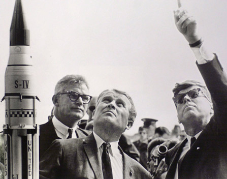 President Kennedy shown pointing at the sky with two other men