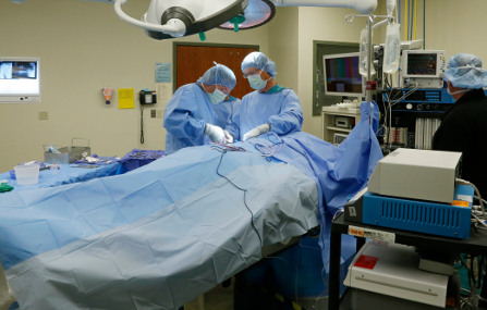 Operation room shows two doctors in scrubs working over a covered patient