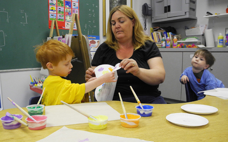 Teacher Julie Singleton helps her 4-year-old students paint butterflies at the Sunshine School in Marietta, Ga